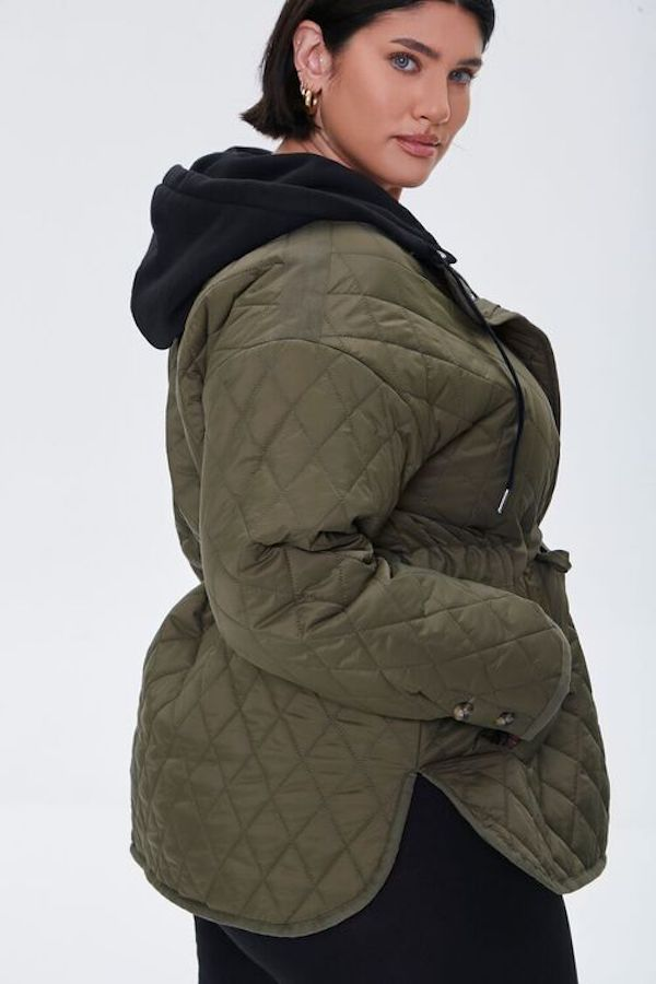 A model wearing a plus-size quilted jacket in olive green.
