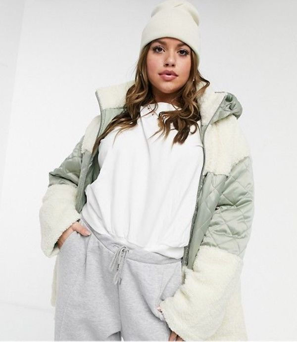 A model wearing a plus-size quilted jacket in green and cream.