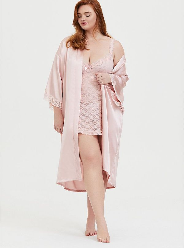 A model wearing a satin robe in pink.