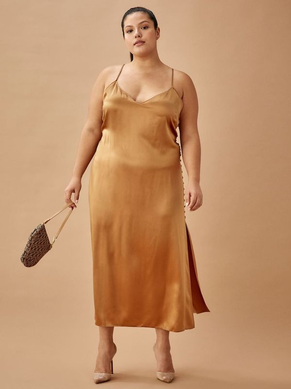 A model wearing a plus-size sexy winter dress in gold.
