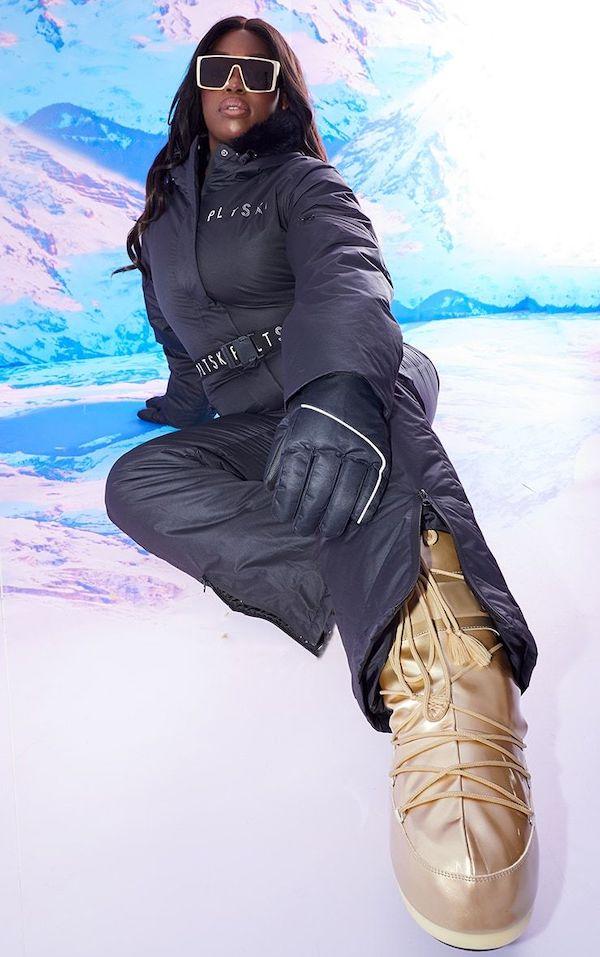 A model wearing a plus-size ski suit in black.