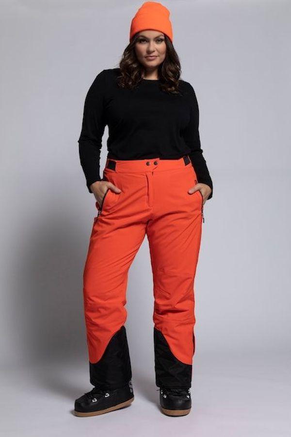 A model wearing a plus-size ski pants in dark orange.
