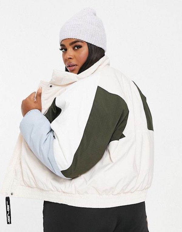A model wearing a plus-size ski jacket in white, green, and blue.