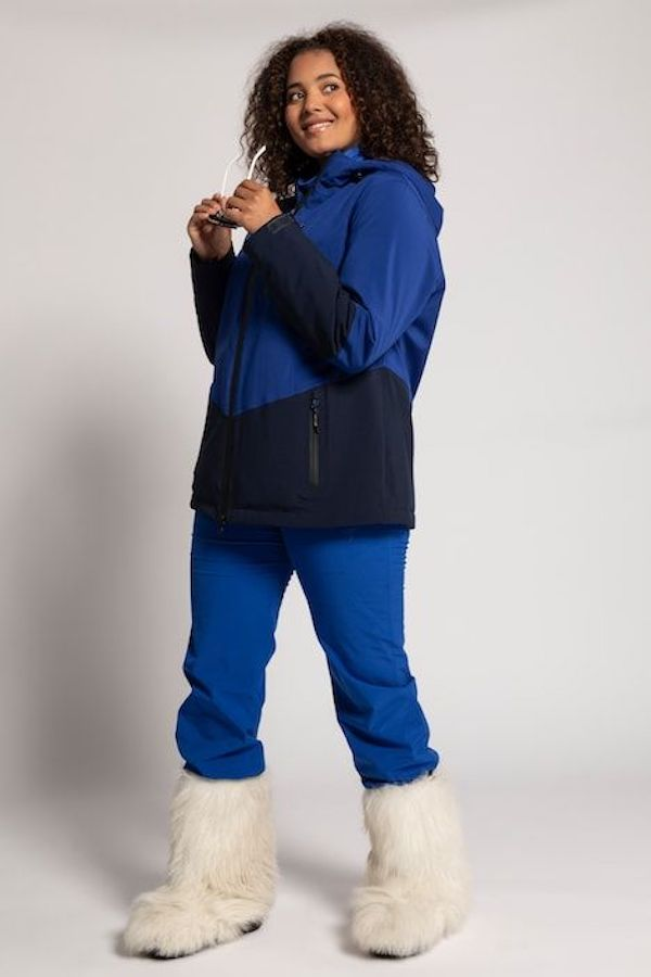 A model wearing a plus-size ski outfit in blue.