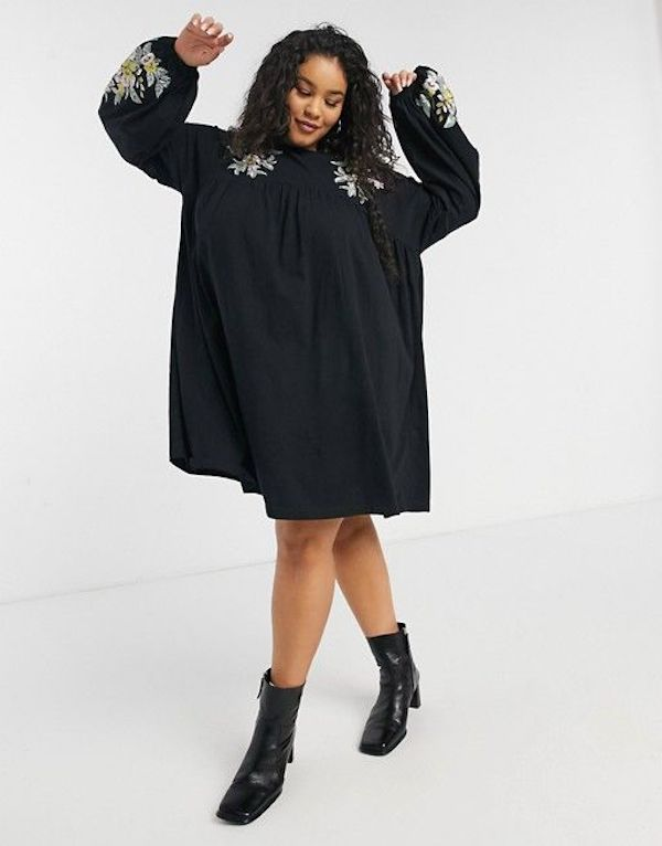 A model wearing a plus-size smock dress in black.