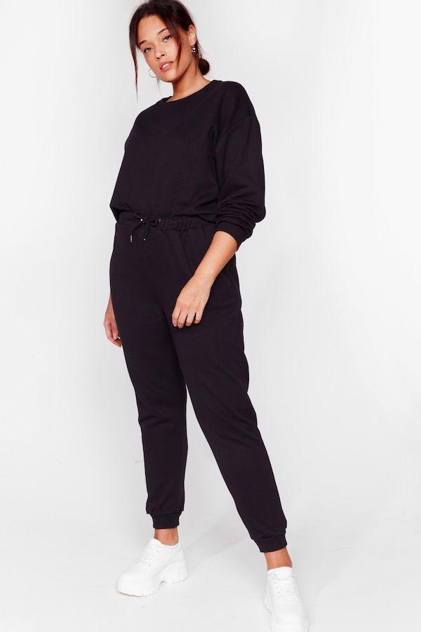 A model wearing a plus-size sweatsuit in black.