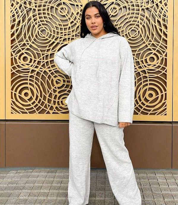 A model wearing a plus-size sweatsuit in white.