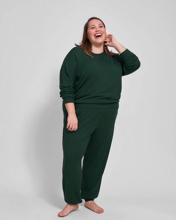 A model wearing a plus-size sweatsuit in green.