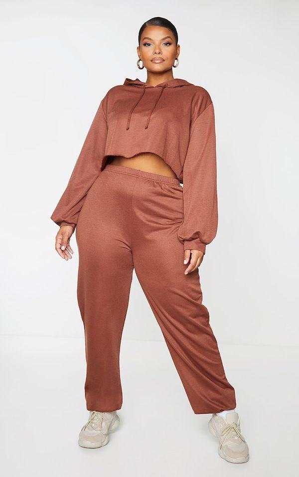 A model wearing a plus-size sweatsuit in brown.