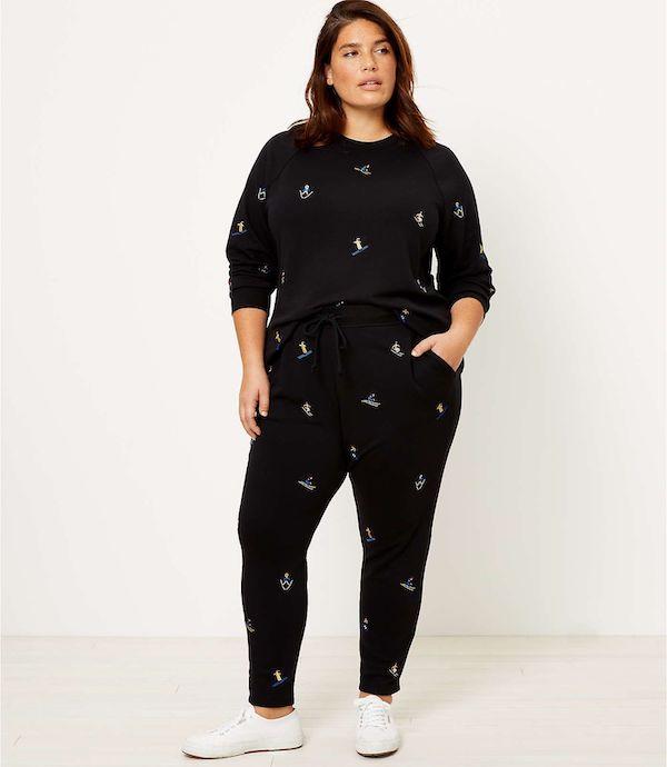 A model wearing a plus-size sweatsuit in ski print.