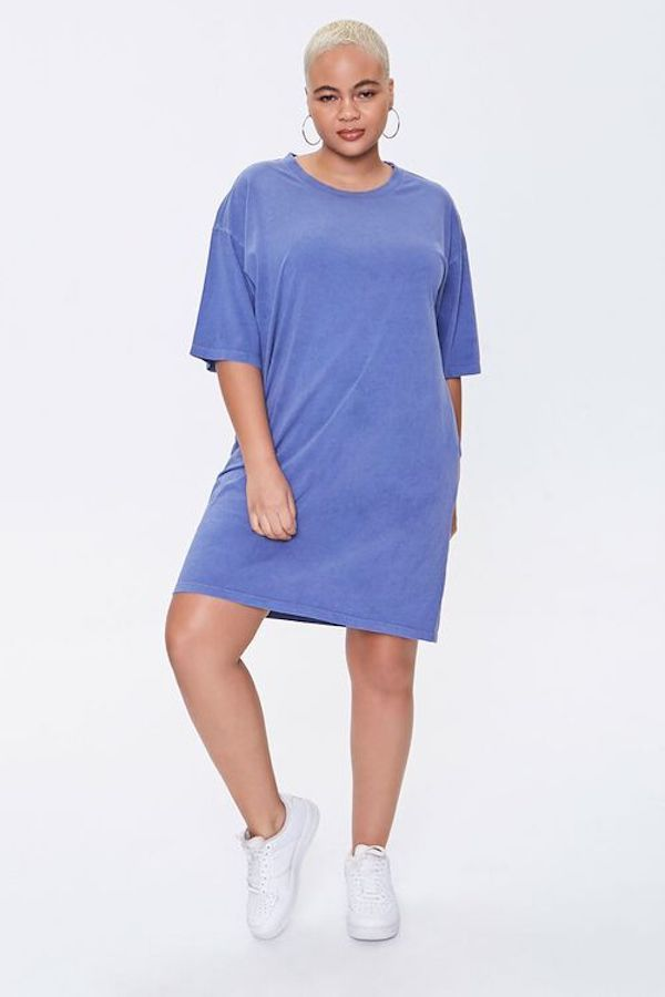 A model wearing a plus-size t-shirt dress in periwinkle.