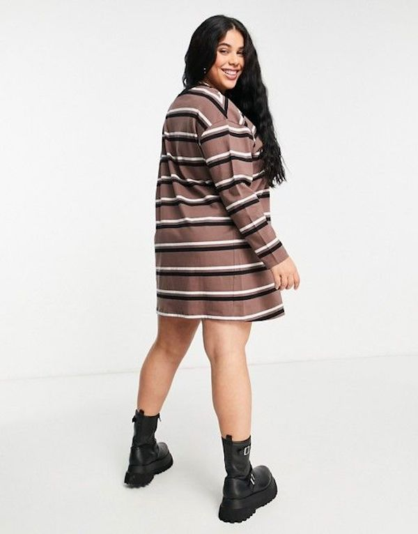 A model wearing a plus-size t-shirt dress in brown stripe.