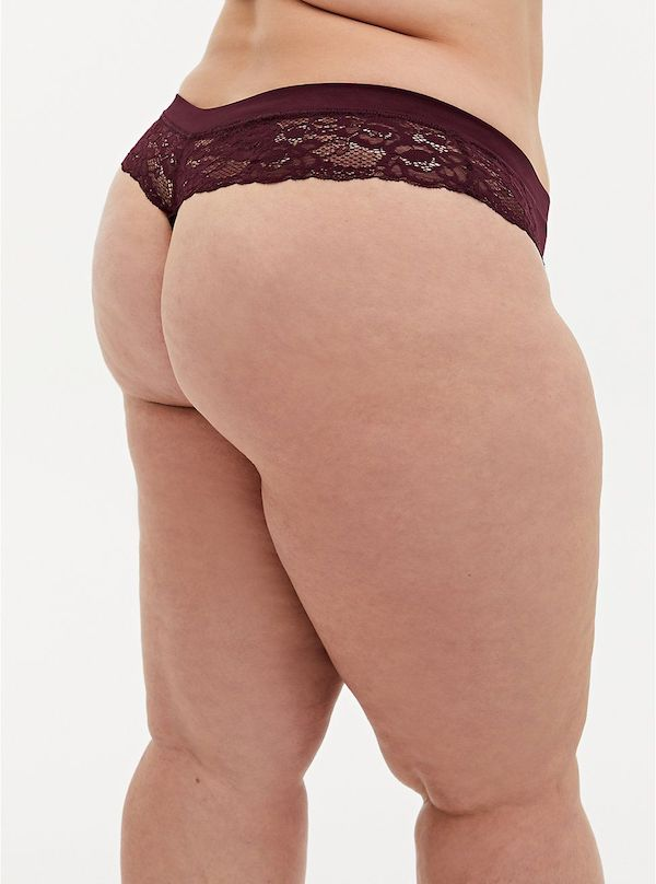 A model wearing a plus-size thong in burgundy.