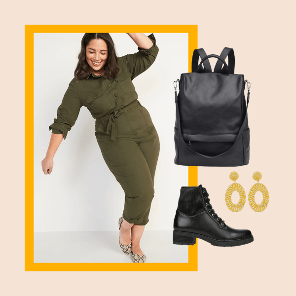 A model wearing an olive green plus-size utility jumpsuit, black booties, black backpack, and statement earrings.