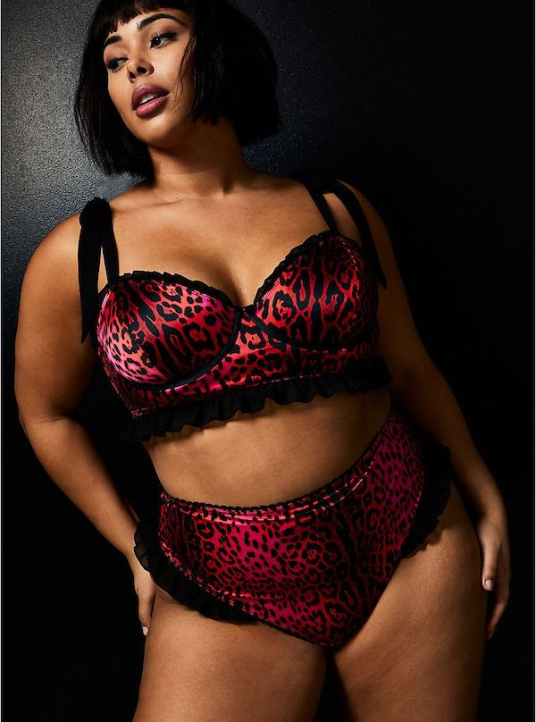 A model wearing a plus-size red and black bralette.