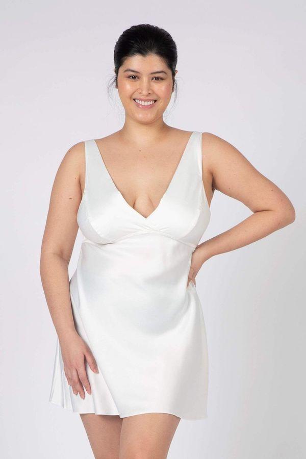 A model wearing a plus-size white slip dress.