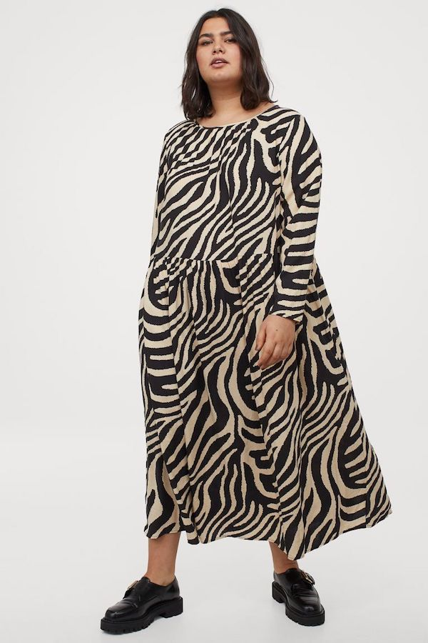 A model wearing a plus-size maxi dress in zebra print.