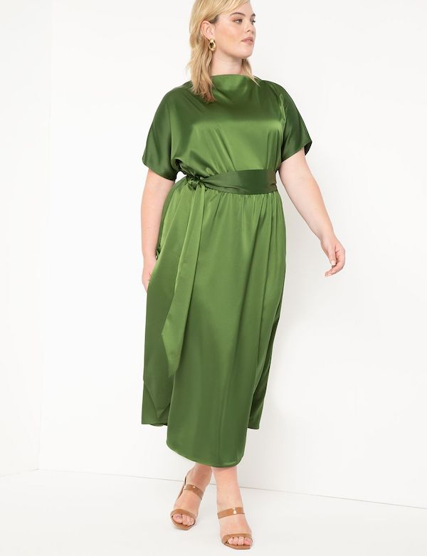 A model wearing a plus-size maxi dress in green.