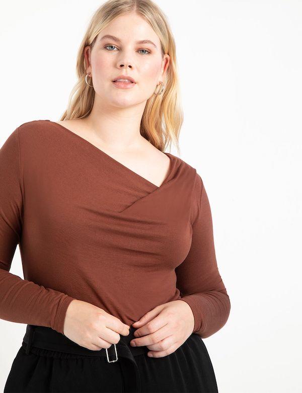 A model wearing a plus-size asymmetric top in brown.