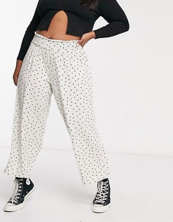 A model wearing plus-size beach pants in white and black polka dot.