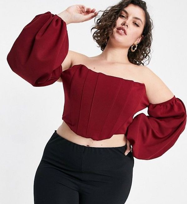 A model wearing a plus-size bustier top in red.