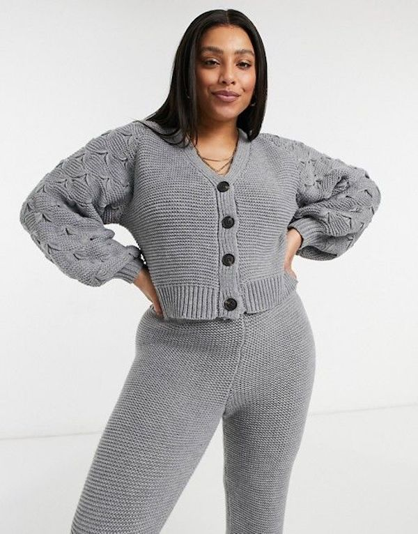 A model wearing a plus-size cropped cardigan.