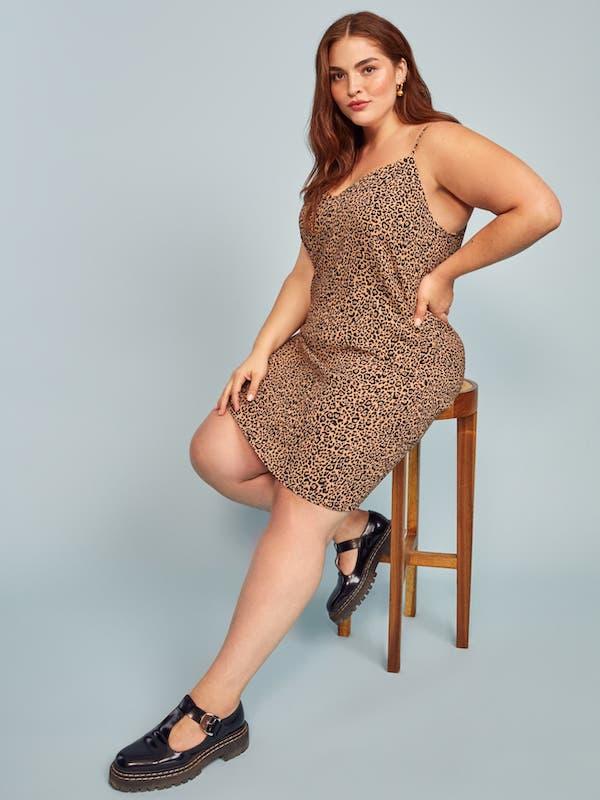 A model wearing a plus-size mini dress in leopard print.