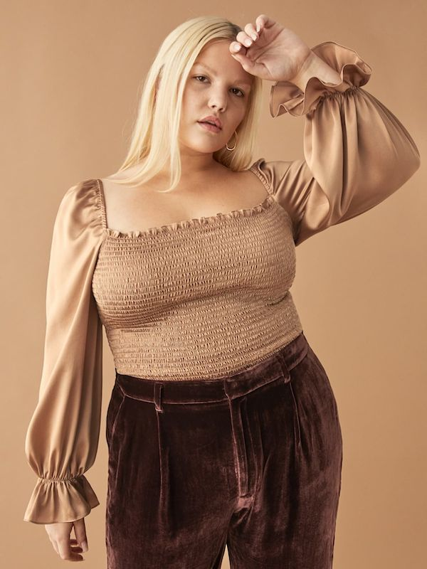 A model wearing a plus-size top in gold.