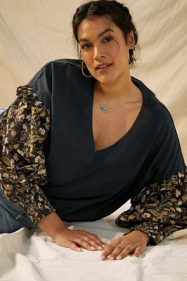 A model wearing a plus-size top in black with ruffle sleeves.