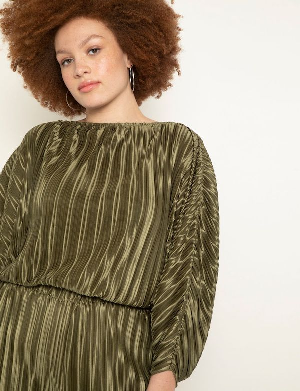 A model wearing a plus-size top in olive.