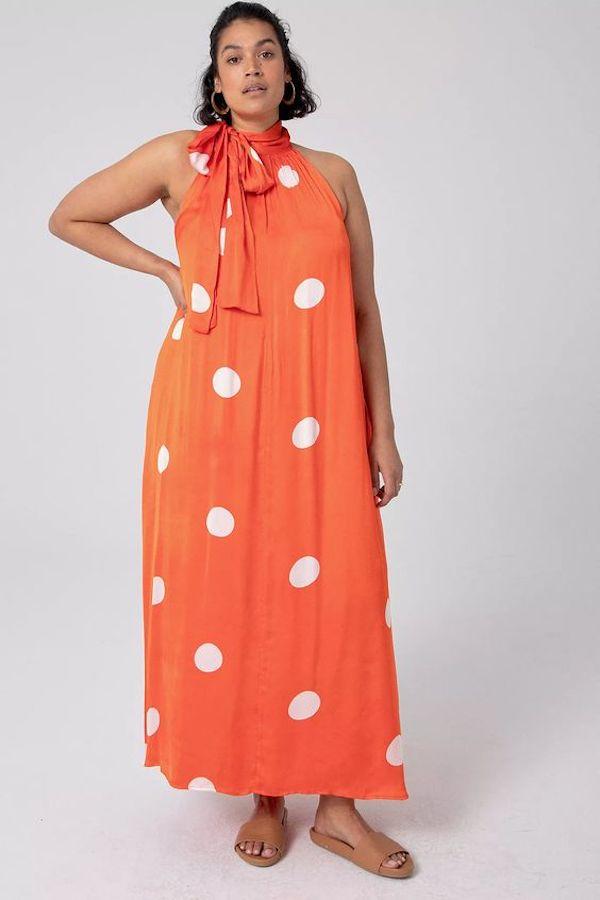 A model wearing a plus-size halter dress in orange.