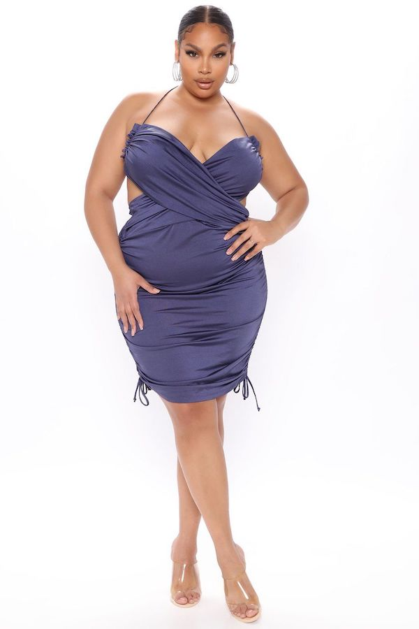 A model wearing a plus-size halter dress in blue.
