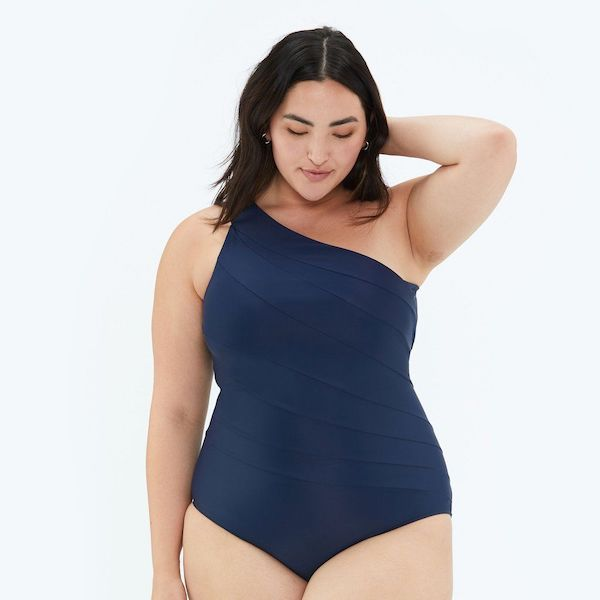 A model wearing a plus-size one-shoulder swimsuit in navy.