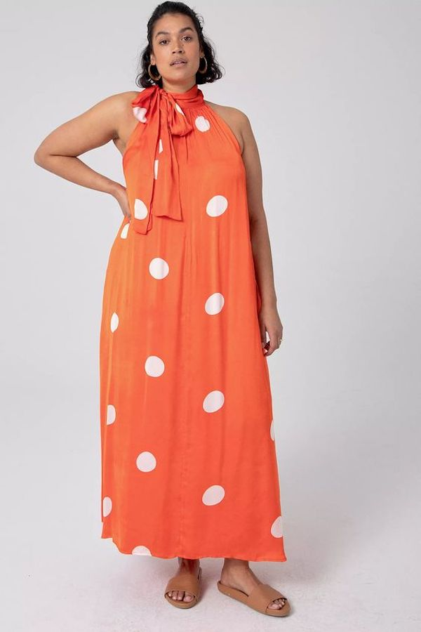 A model wearing a plus-size polka dot dress in orange.