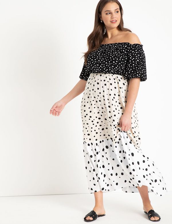 A model wearing a plus-size polka dot dress in black and white.