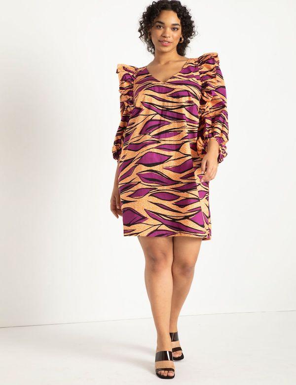 A model wearing a plus-size ruffle dress in purple leaf print.