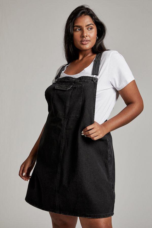 A model wearing a plus-size pinafore dress.