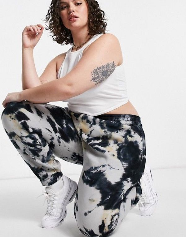A model wearing plus-size tie-dye sweatpants.