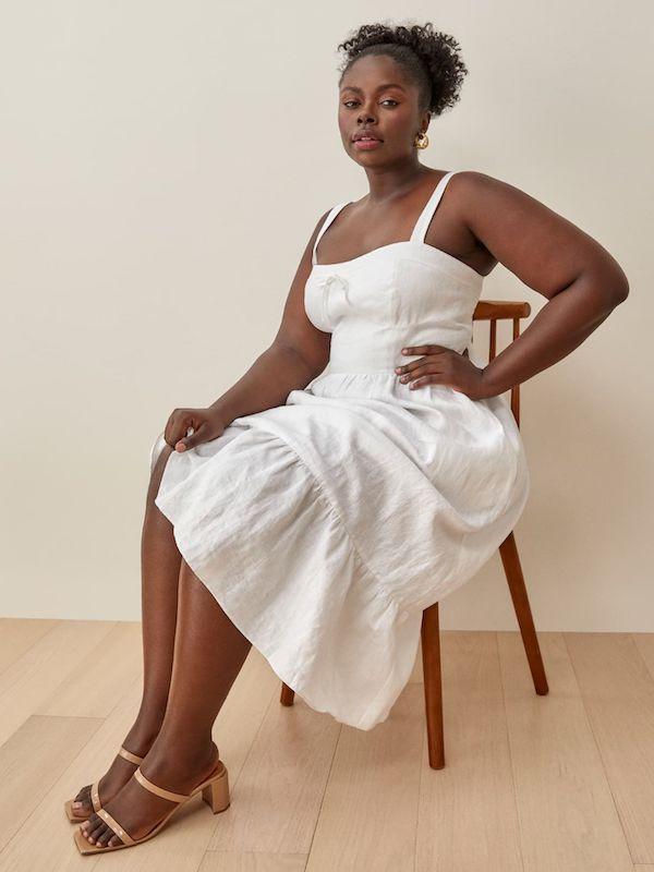 A model wearing a plus-size white dress.
