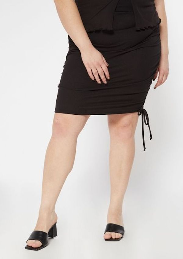 A model wearing a plus-size ruched skirt.