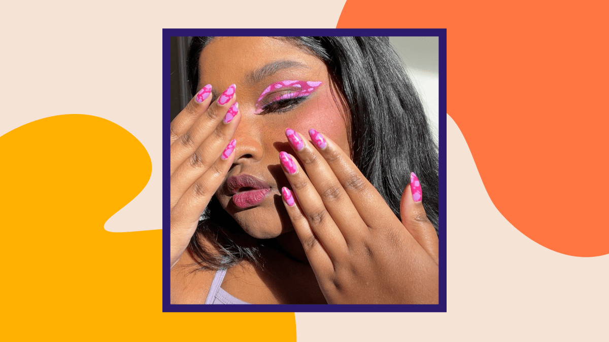 An influencer with pink cow print nails and eye makeup.