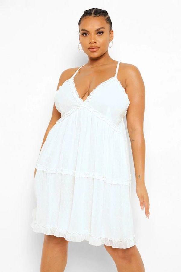 A model wearing a plus-size white party dress.