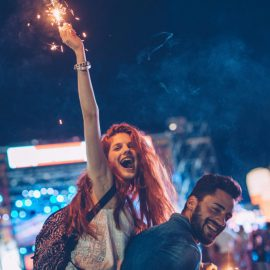 A young couple embracing at an outdoors music festival. They holding sparklers in summer night.
