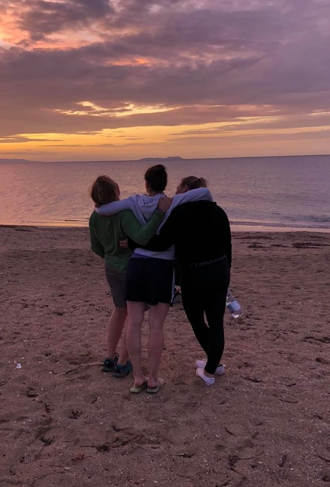 3 friends looking over the sea at sunset laughing, My best memory from the yoga retreat.