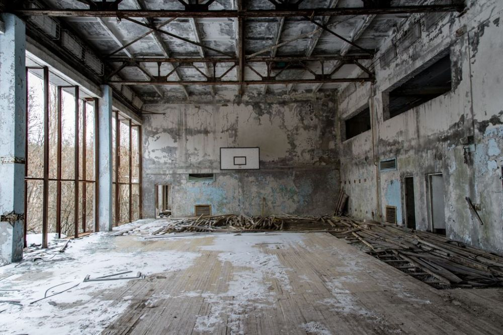 Image of a decaying indoor basket ball pitch in the city of Prypiat.
