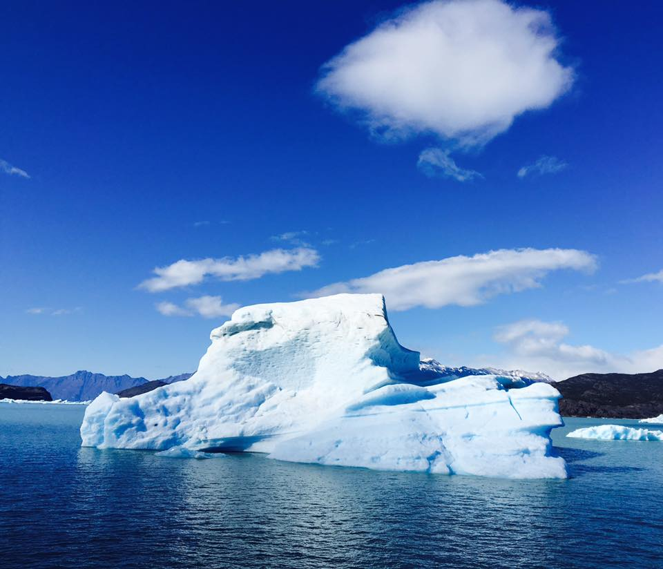 Photo of a white bright iceberg contrasted against the azure waters of Lago Argentino
