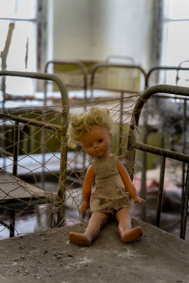 Eerie photo of a dirty doll, missing an eye, sitting on one of the abandoned bunk beds at the Kopachi Kindergarten.