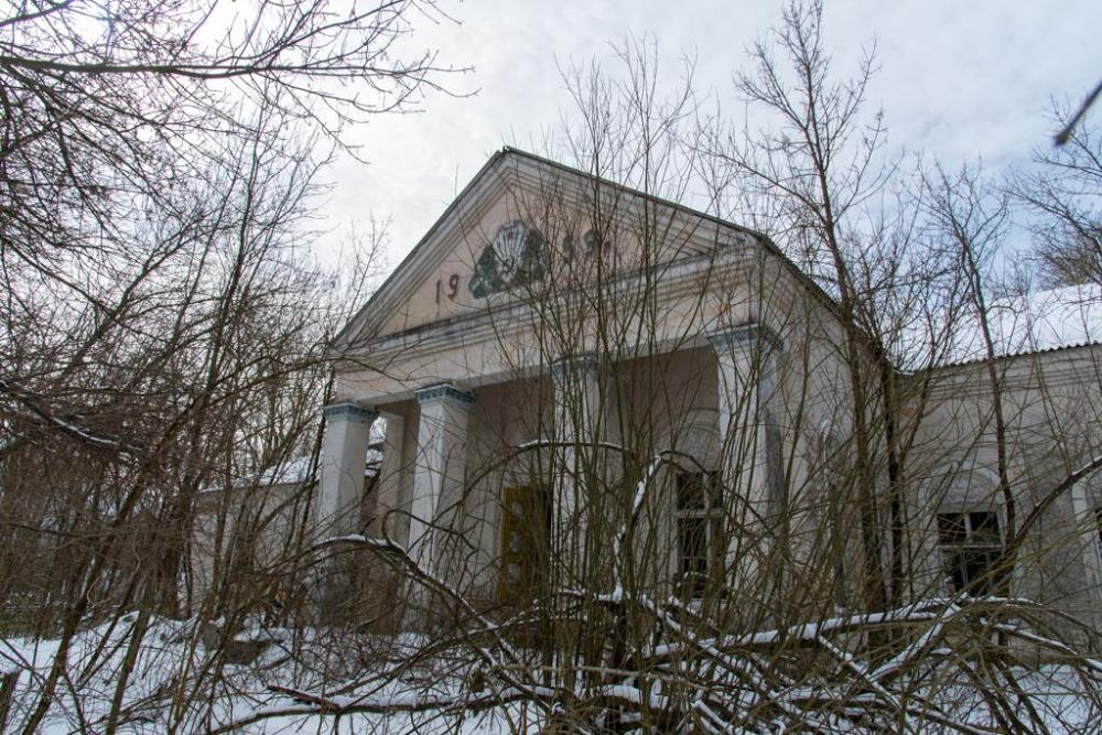 Photo of the Palace of Culture in a small village within the 30 km Chernobyl Exclusion zone. An imposing building with large white large pillars, still standing strong amongst the overgrown trees.