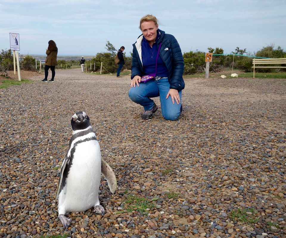 Photo of Bea kneeling behind a penguin who is inquisitively looking into the camera.