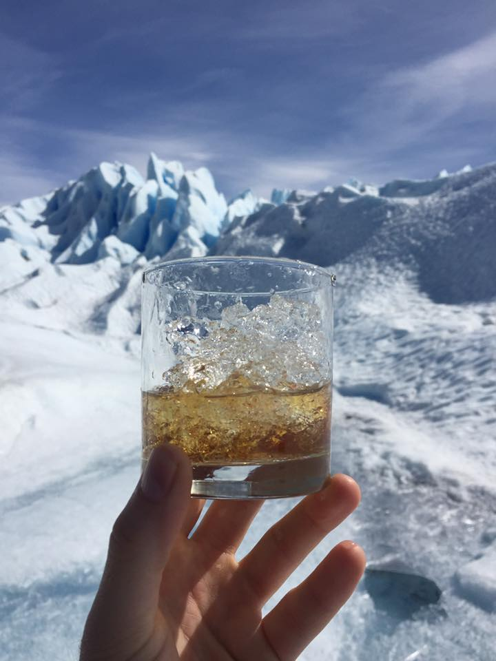 Photo of Doug's hand holding a glass of whiskey with glacial ice.